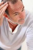Senior man concerned about hair loss Royalty Free Stock Photography