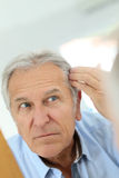 Senior man concerned about his hair loss Royalty Free Stock Images