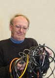 Senior man confused by tangled wires. Senior man confused and frustrated by badly tangled wires Stock Image
