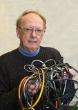 Senior man confused by tangled wires. Senior man annoyed and confused by completely tangled wires Stock Photo
