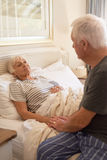 Senior man consoling of his sick wife in bed Royalty Free Stock Images