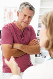 Senior man in consultation room with doctor stock photo