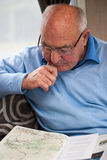 Senior man in contemplation. Senior man looking at a magazine and in contemplation Stock Photos