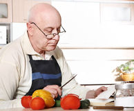 Senior man cooking Royalty Free Stock Images
