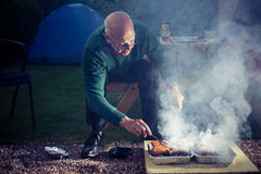 Senior man cooking on a barbecue Stock Image