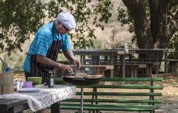 Man cooking barbecue on safari royalty free stock photo