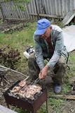 Senior man cooking catfish Stock Photo