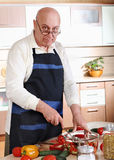 Senior man cooking in kitchen Royalty Free Stock Photos