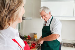 Senior man cooking in kitchen Royalty Free Stock Images