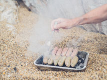 Senior man cooking sausages on the beach Stock Images