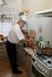 Senior man coooking Stock Photography