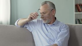 Senior man on couch looking aside and smiling, life experience and wisdom. Stock footage stock footage