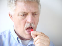 Senior man with cough drop Royalty Free Stock Photography