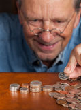 Senior man counting cash into piles. Senior retired caucasian man counting out cash into piles Royalty Free Stock Image
