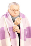 Senior man covered with blanket and neckwear coughing because of Royalty Free Stock Photography