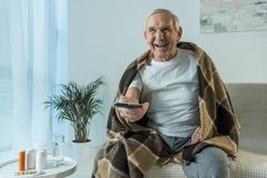 Senior man covered in plaid watches tv during sickness in room with medications royalty free stock photography