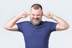 Senior man, covering closed ears annoyed by loud noise not wanting to hear story royalty free stock images
