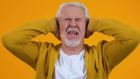 Senior man covering ears by hands tired of loud conversation noise, pressure. Stock footage stock video