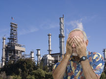 Senior man covering eyes in front of refinery. Old man refusing to see pollution from refinery Stock Images