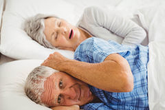 Senior man covering her ears while man snoring Royalty Free Stock Photography