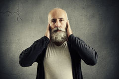 Senior man covering his ears and looking at camera Royalty Free Stock Photos