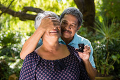 Senior man covering woman eyes while gifting her ring Stock Images