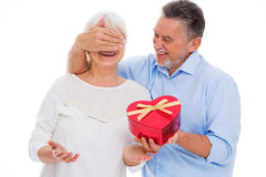 Senior man covering woman`s eyes and holding heart-shaped box Royalty Free Stock Images