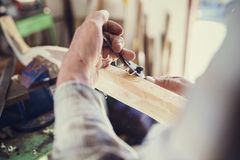 Senior man. Senior craftsman working with planer on wooden pole in his workshop Royalty Free Stock Photos