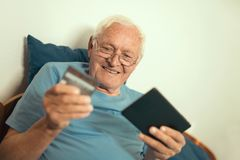 Senior man with credit card for on line banking Royalty Free Stock Image