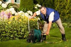 Senior man crimping hose in the garden. Senior man crimping water hose in the garden royalty free stock photography