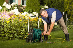 Senior man crimping hose in the garden Royalty Free Stock Images
