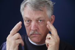 Senior man crossing his fingers Stock Photo