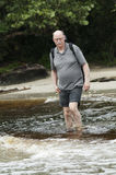 Senior man is crossing a river Stock Photos
