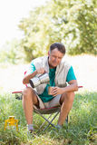 Senior man is crouching beside his tent. In a forest Royalty Free Stock Image