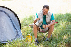 Senior man is crouching beside his tent. In a forest Royalty Free Stock Photography