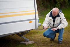 Senior Man Crouching While Repairing Caravan Stock Image