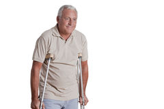 Senior Man with Crutches. And females doing physical exercise Stock Photography