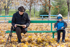 Senior man on crutches reading with his grandson. Senior men on crutches reading a book with his little grandson sitting on the opposite end of the wooden park Royalty Free Stock Image