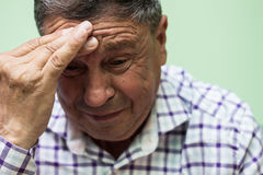 Senior man crying. Looking down, living room royalty free stock photography