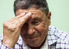 Senior man crying. Looking down, living room royalty free stock images