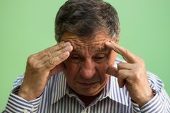 Senior man crying. Sitting in the living room stock photography