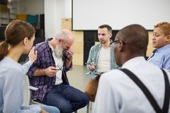 Senior Man Crying in Support Group. Portrait of senior men crying during group therapy session with mature psychologist, copy space royalty free stock image