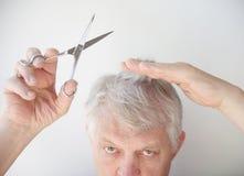 Senior man cuts hair Stock Photo