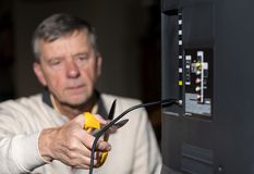 Senior man cutting the cord on his cable TV package. Close up of senior caucasian retired man cutting the aerial connection to his TV to illustrate cutting the Stock Photography