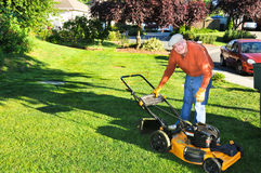 Senior Man Cutting Grass. Active, mature white male sweating as he leans over lawn mower to reattach cuttings catcher in front yard of a suburban residential Royalty Free Stock Photos