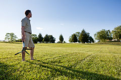 Senior man cutting grass with shears Royalty Free Stock Image