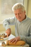 Senior man cutting pie Royalty Free Stock Photography