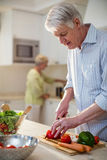 Senior man cutting vegetables for salad Royalty Free Stock Image