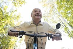 Senior man on cycle ride in countryside. Senior caucasian man on cycle ride in countryside. Green trees on background. He is happy and active Royalty Free Stock Image
