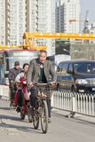 Senior man cycles in busy Beijing downtown, China Stock Photo